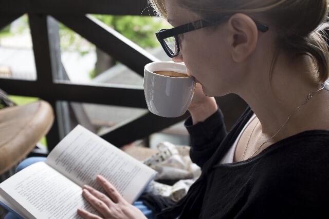 コーヒーを飲んで本を読む女性