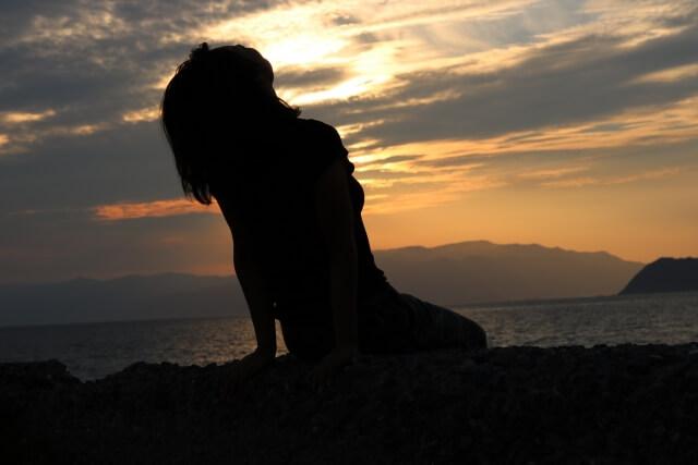 夕日に当たりながら体を風に預ける女性