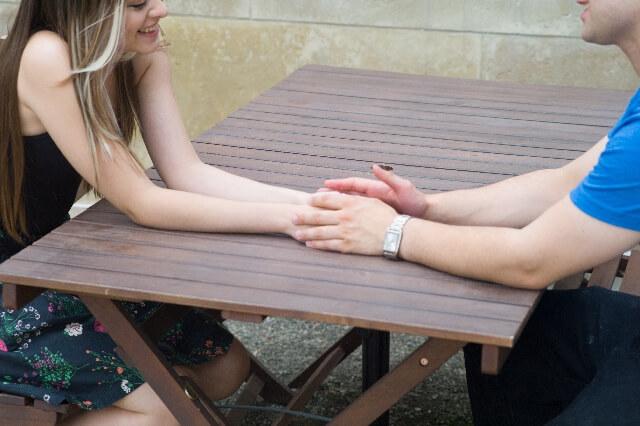 テーブルを挟んで手を握るカップル