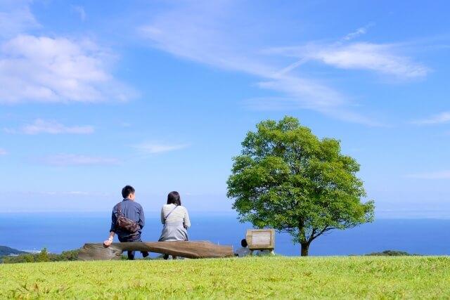 青空のもとベンチに座るカップル
