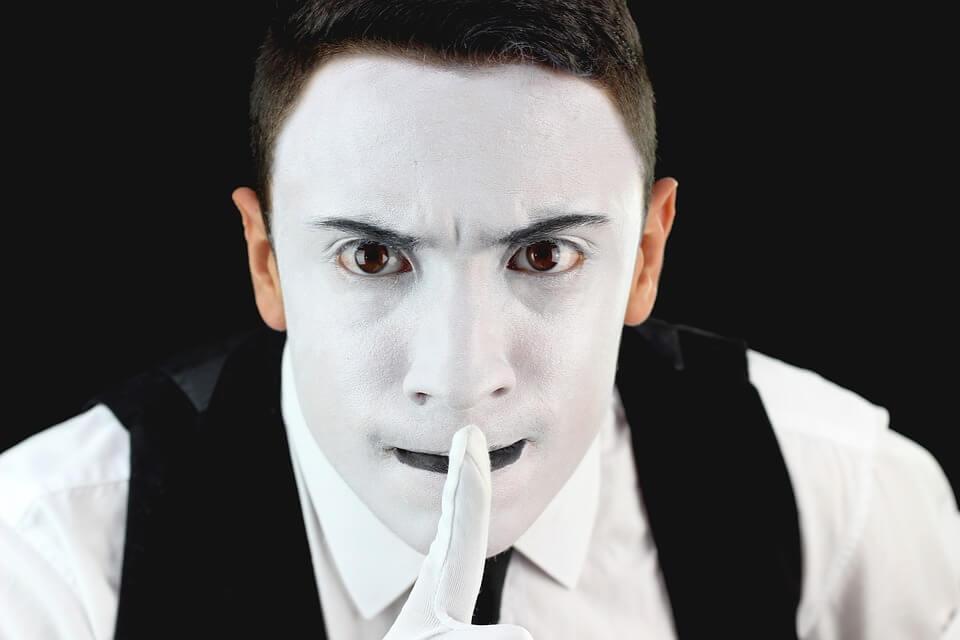 人差し指を口の前に持ってくる男性