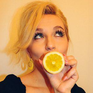 レモンを口の前に持ってきて斜め上を向く女性