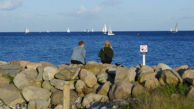 海岸で海を見つめるカップル