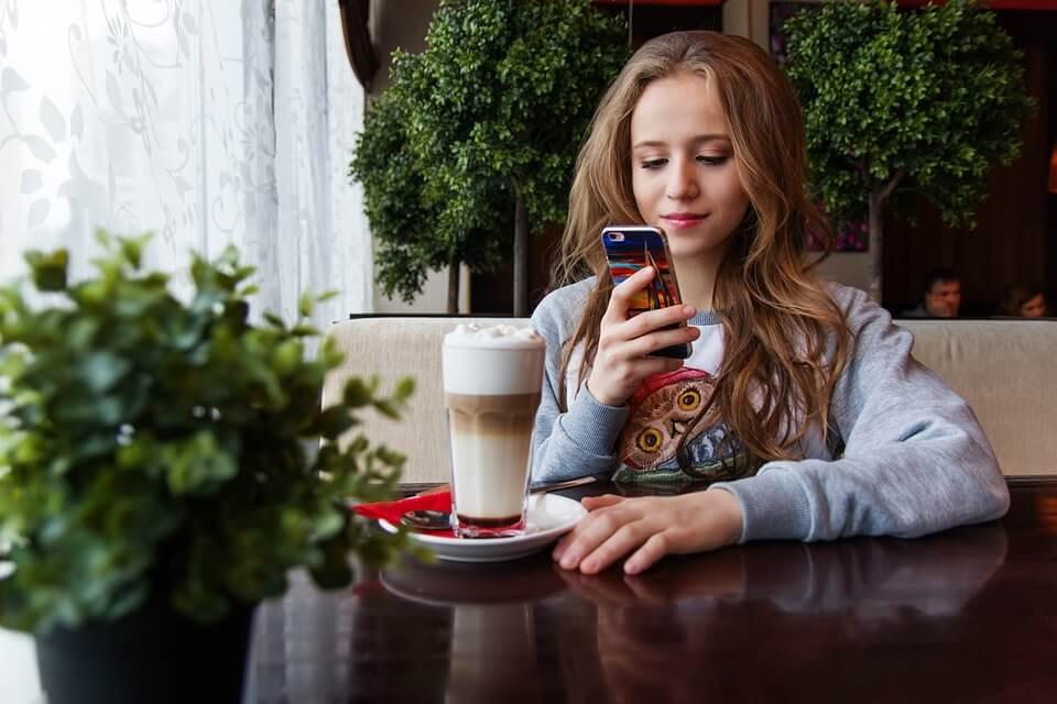 スマホを見てほほ笑むカフェにいる女性
