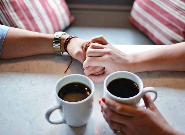 コーヒーの入ったコップのカップルの手