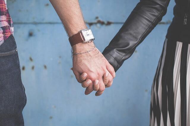 手をつなぐスタイリッシュな服を着たカップル