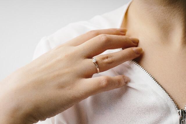 手で鎖骨に触れる女性