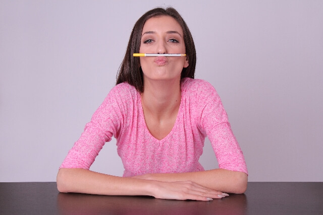 鉛筆を口の上にのせる女性