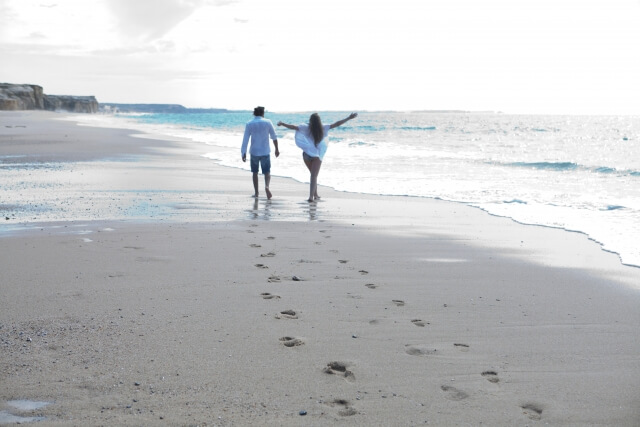晴れの日に浜辺を歩くカップル