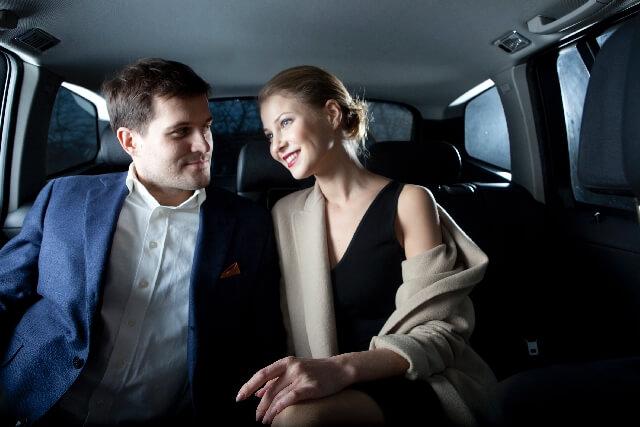 リムジンの車内で話す金持ちカップル