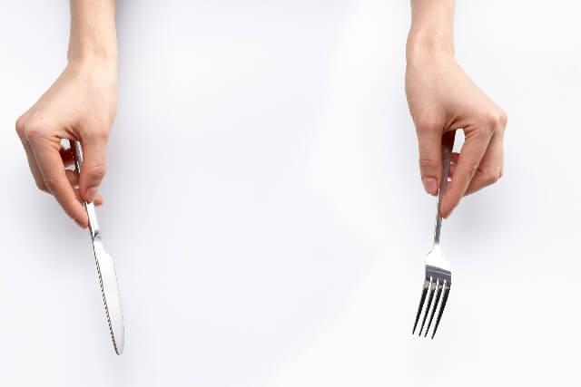 フォークとナイフを手に持つ女性