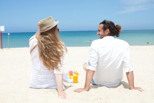 海辺の砂浜でリラックスするカップル