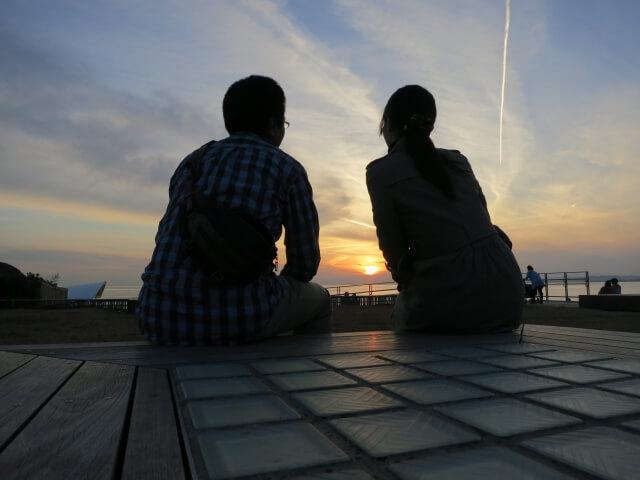 夕日をバックに寄り添うカップル