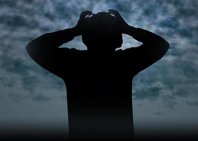 曇天のもと頭を抱える男性