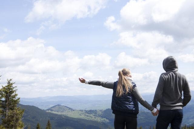 手をつなぎながらハイキングに出かけるカップル