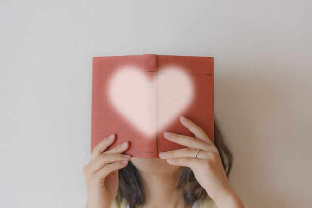 ハート型のブックカバーの本を読む女性