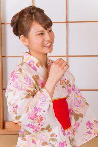 ピンクの着物を着ておしとやかに笑う女性