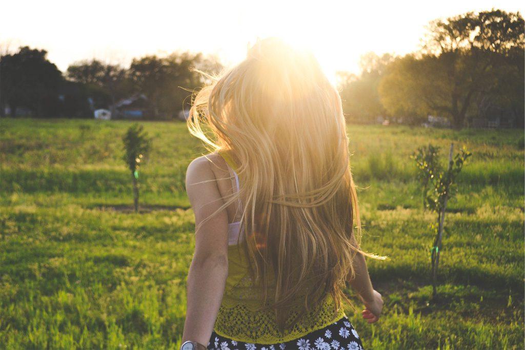 太陽に向かって歩く女性