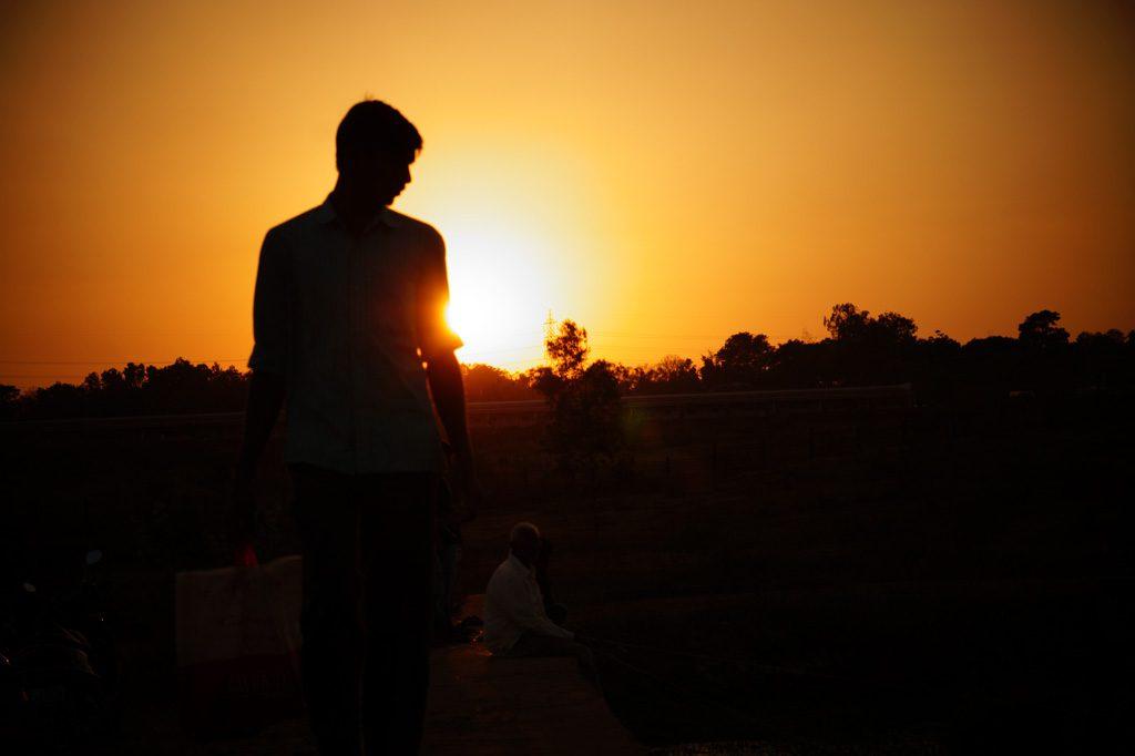 日の入りを見つめる男性