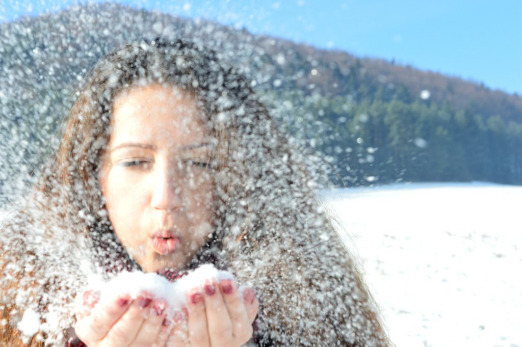雪を吹く女性