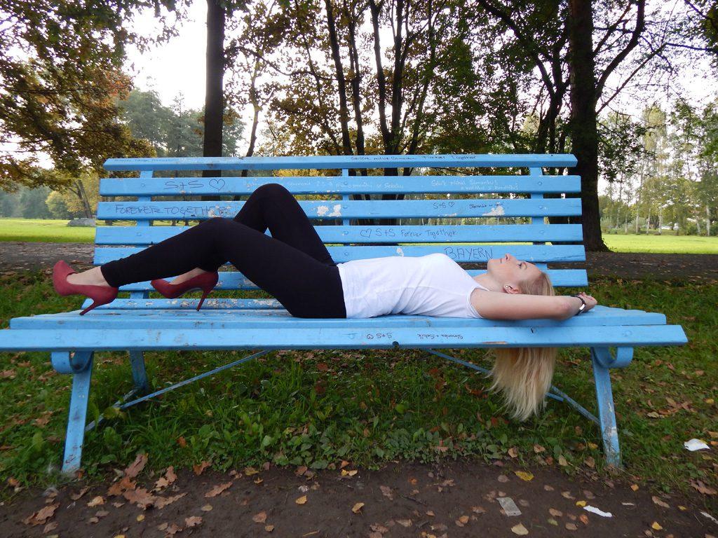 ベンチに横たわる女性