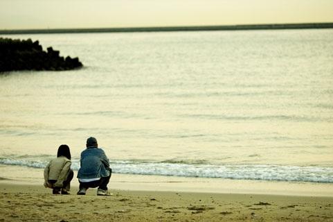 浜辺で座って話すカップル