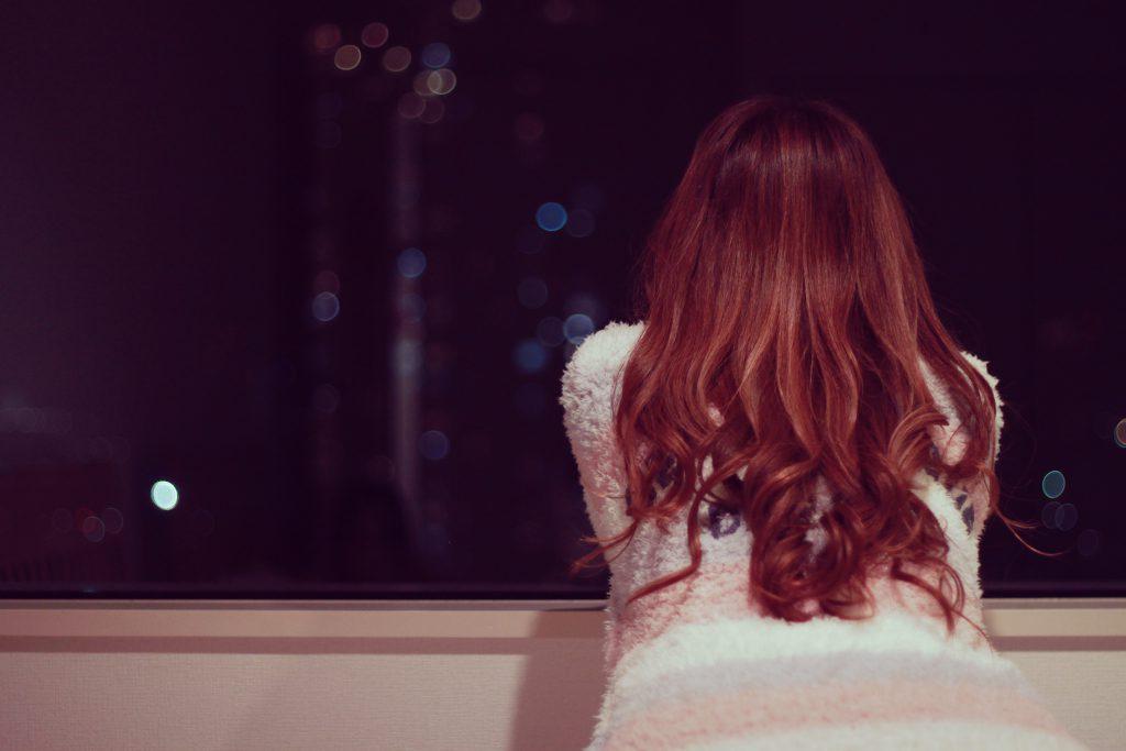 寝る前にひとり夜景を眺める女の子