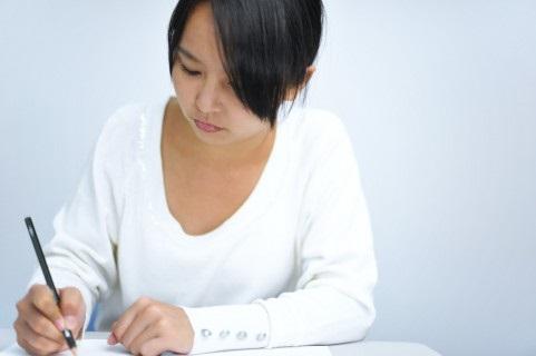 紙に不安を書き出す女性
