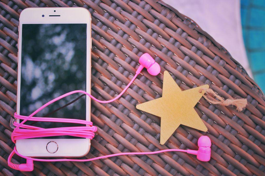 iPhoneとピンクのイヤホン