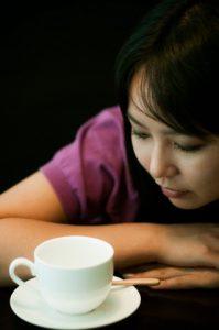 コーヒーカップを見つめて悩む女性