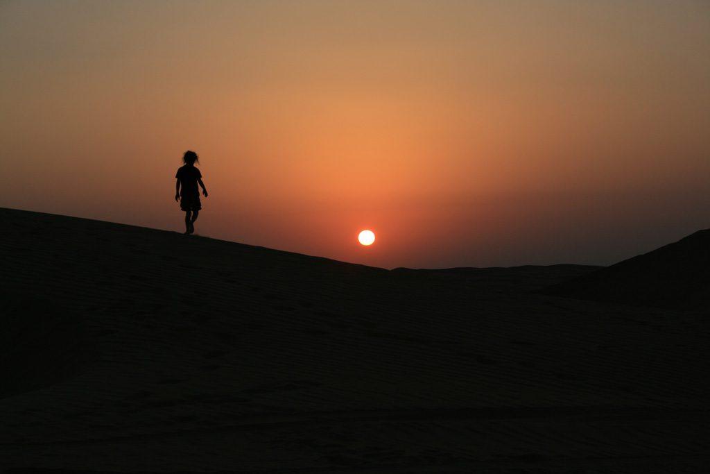 夕日に向かって歩く女性