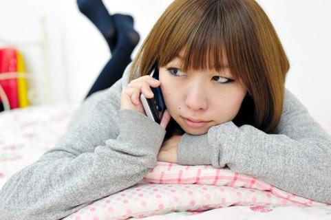 寝転がりながら電話する女性