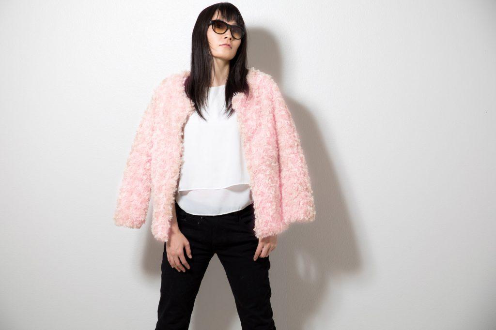 ピンク色のプードルコートを着た女性