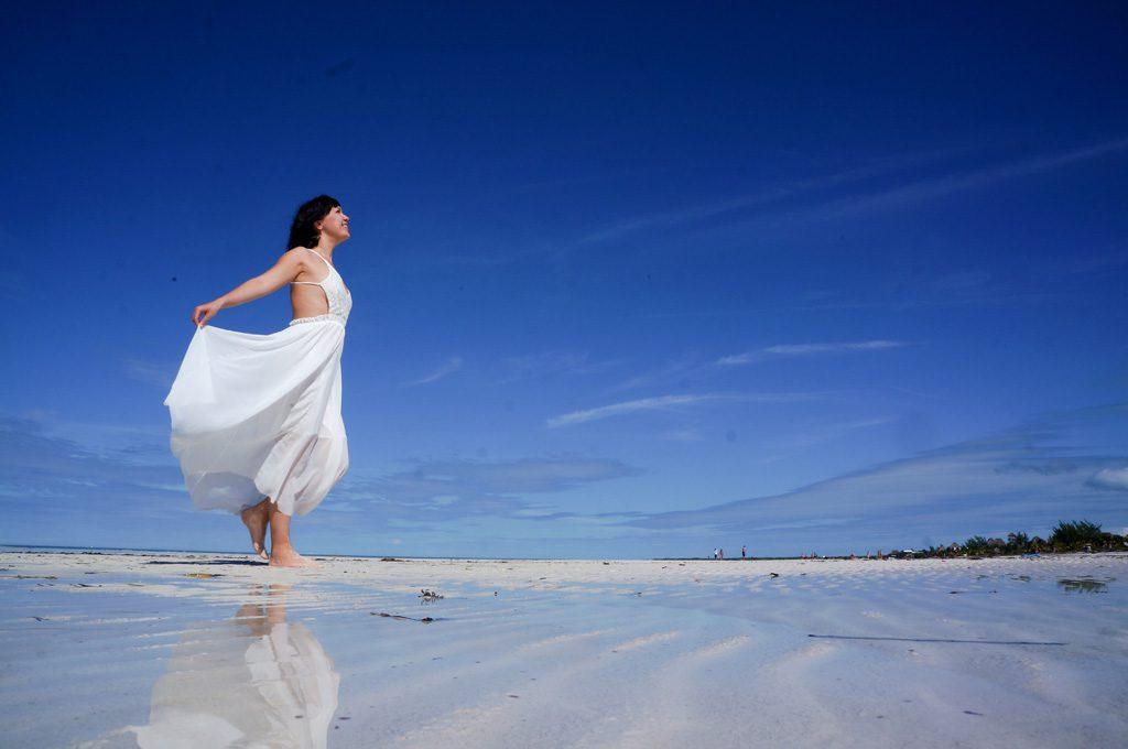 砂浜を笑顔で歩く女性
