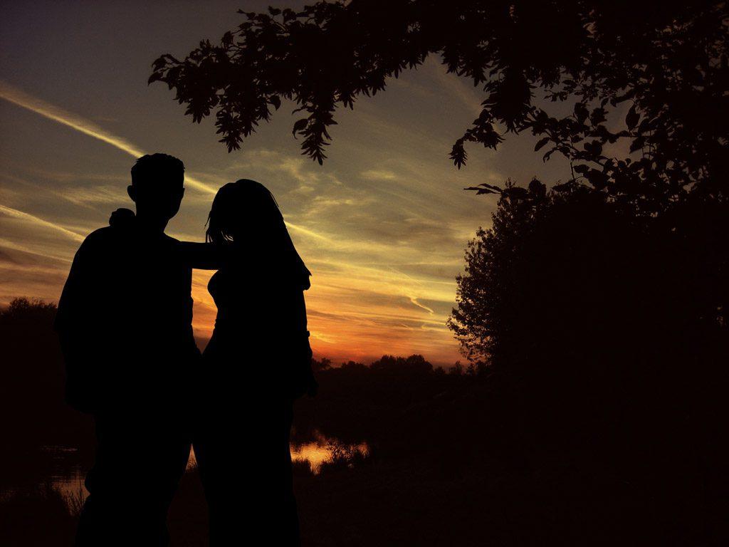 夕日に映るカップルの後ろ姿