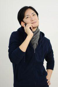 呆れながら電話に出る男性