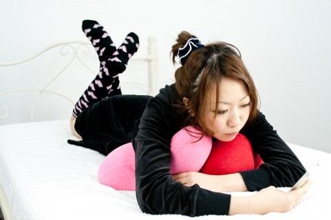 横になりながらスマホをいじる女性