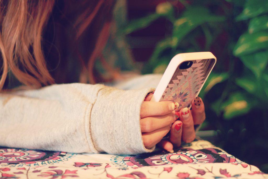 寝転んでスマートフォンを操作する女の子