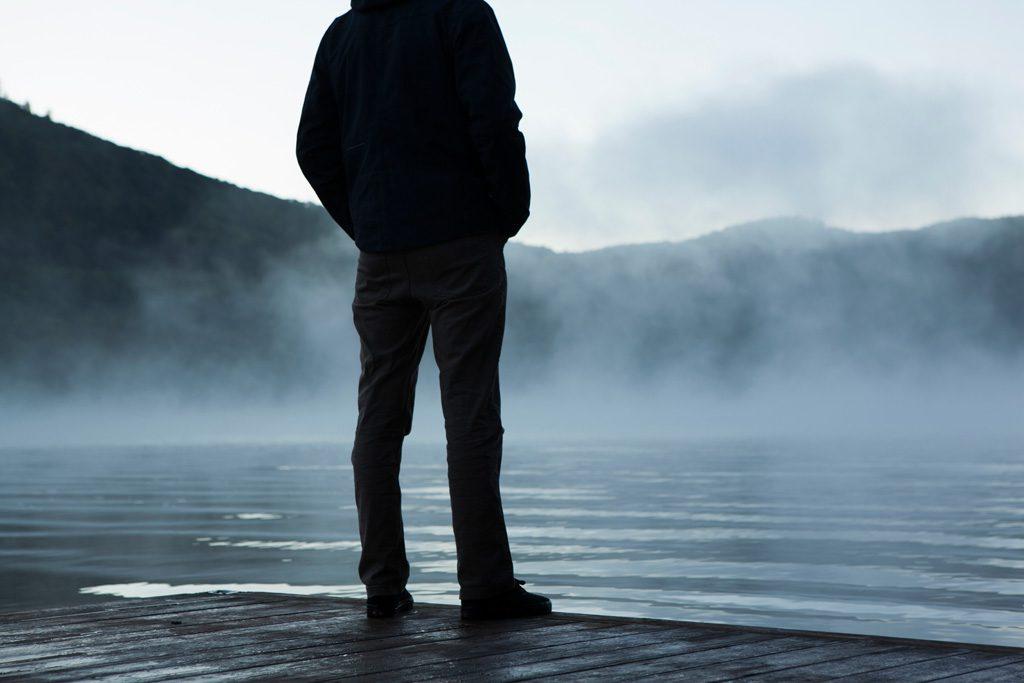 湖の前で立ちつくす男性