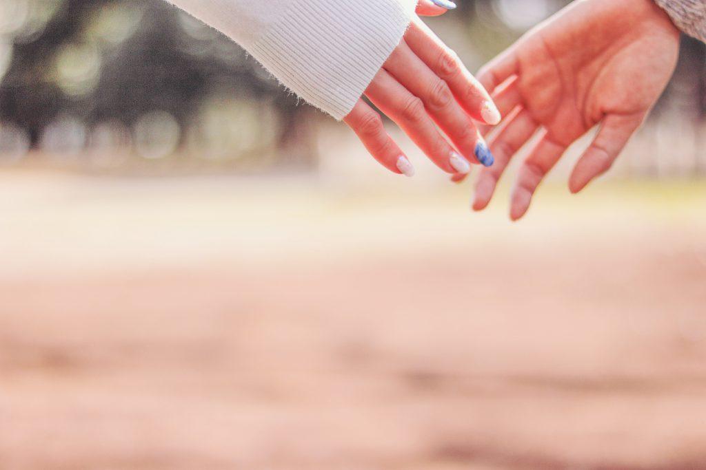 女性の手をつなごうとする男性