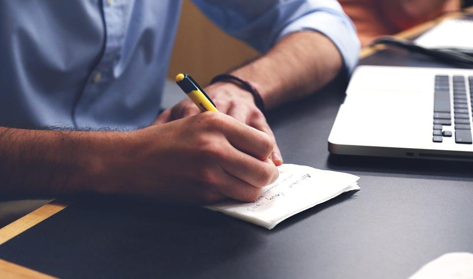 紙に書く男性