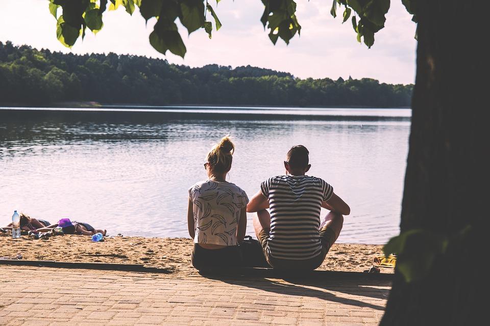 湖で座り込むカップル