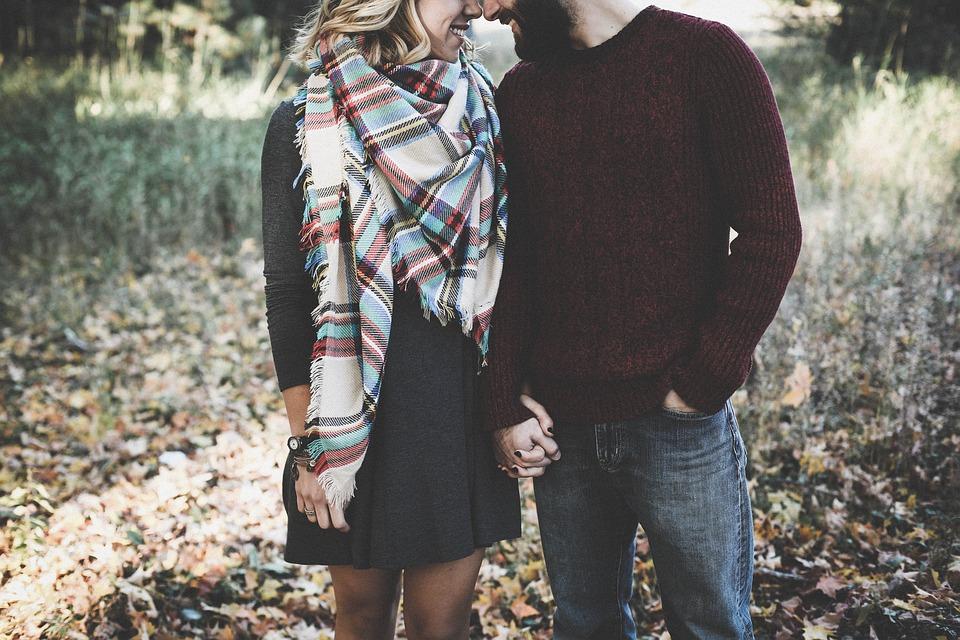 手をつなぎ顔を近づけるカップル