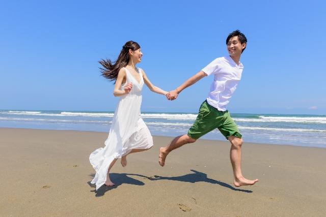 海で女性の手を引く男性