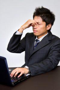 PCのやり過ぎで目が疲れるビジネスマン