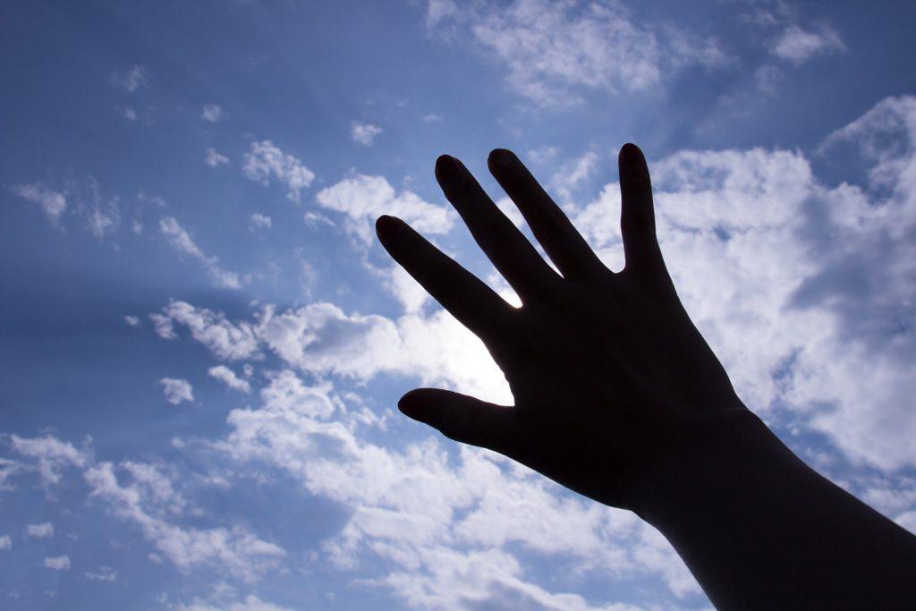 太陽を手で隠す女性