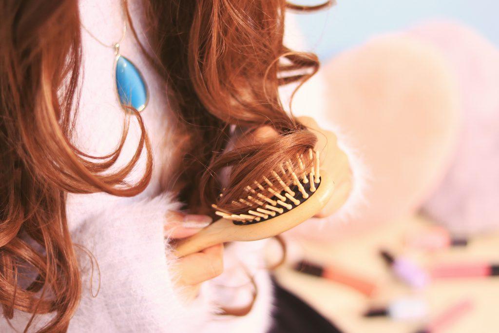 ブラシで髪の毛を丁寧にとかしている女の子