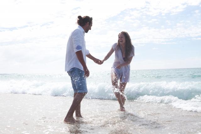 浜辺ではしゃぐカップル