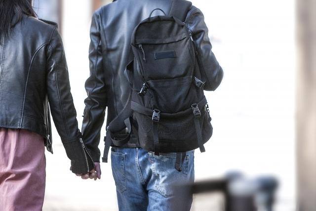 手をつないで歩くカップルの後ろ姿