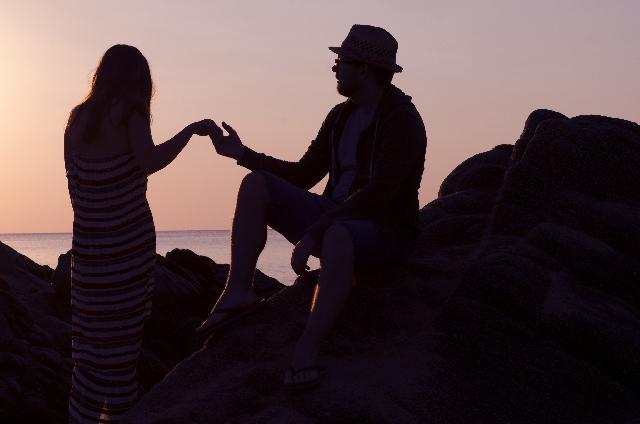 夕暮れに手を取り合うカップル